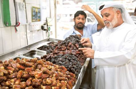 An Emirati selects the variety of dates on a display at a date shop at Mina Market in Abu Dhabi. As a food hub, the UAE can export more of its national produce. Image Credit: Abdul Rahman/Gulf News Archives