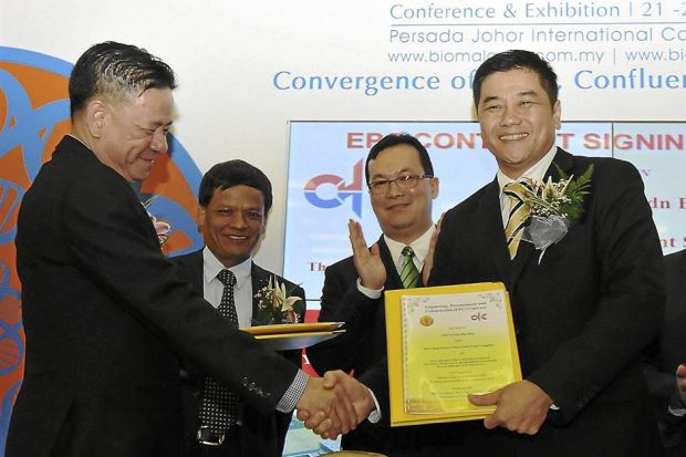 Pham (left) exchanging documents with Chang. With them are Nguyen (2nd from left) and Malaysia Biomass Industries Confederation presiden t Datuk Leong Kin Mun.