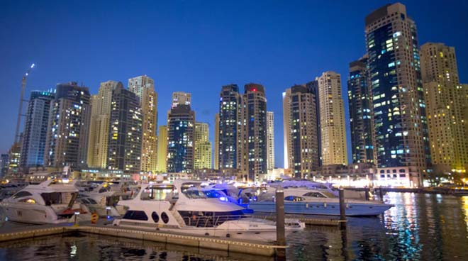 Luxury yachts are seen surrounded by skyscrapers as the sun sets over Dubai Marina, in Dubai. The second-richest member of the United Arab Emirates is one of four cities competing for the world fair, which will be awarded today by the Bureau International des Expositions in Paris.
