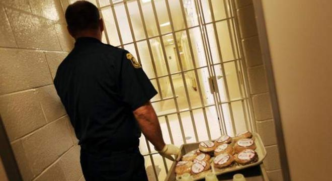 Officer Dan Tar takes meals into the jail at the Livonia Police Station in Livonia on Wednesday, June 9, 2010. / SUSAN TUSA/Detroit Free Press