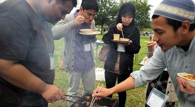 Students from Malaysia and elsewhere enjoy a barbecue in Utsunomiya, Tochigi Prefecture, with beef prepared according to halal rules. (Masanobu Furuya)