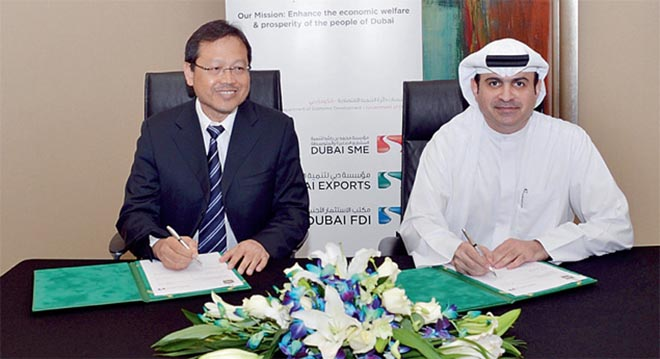 Sami Al Qamzi and Jamil bin Bidin signing the agreement at the 5th Exporters' Forum in Dubai. — Supplied photo