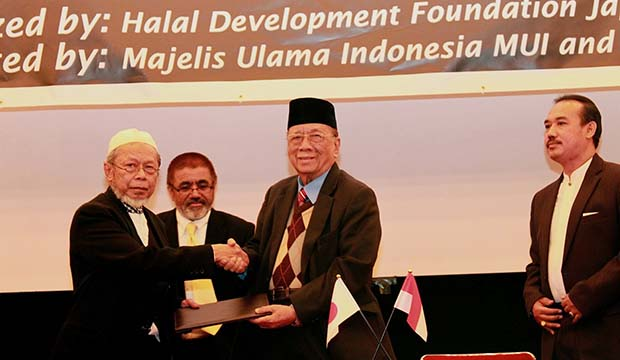 President of HDFJ Idrisno Madjid shaking hands with Drs. Amidhan Shaberah, the MUI Chairman after signing MoU. On most right is Mr. Lukmanul Hakim, Director LPPOM MUI.
