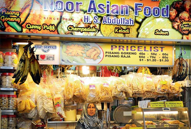 A woman sells halal food at a market in Singapore. Muslims do not control the halal agro-food supply chain, as large non-Muslim owned multinational food companies, from upstream to mid-stream to downstream, are product providers to consumers. — Bloomberg