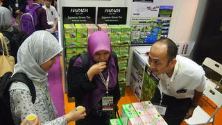 Muslim visitors to the trade show sip green tea from Japan's Harada Seicha. Malaysia's annual halal expo attracts more than 10,000 domestic and foreign exhibitors.