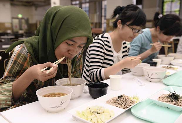 Foreign students, including a woman from Indonesia, eat soba and udon in a newly developed halal broth at a tasting event at the University of Tokyo's Hongo Campus in Bunkyo Ward, Tokyo, on May 26. The Yomiuri Shimbun